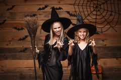 Halloween Concept - cheerful mother and her daughter in witch costumes celebrating Halloween posing with curved pumpkins over bats Stock Images