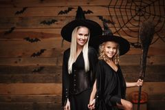 Halloween Concept - cheerful mother and her daughter in witch costumes celebrating Halloween posing with curved pumpkins over bats Stock Photos