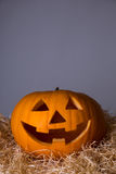 Halloween concept - close up of pumpkin Jack-O-Lantern over grey Royalty Free Stock Photos