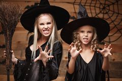 Halloween Concept - Closeup beautiful caucasian mother and her daughter in witch costumes celebrating Halloween posing with curved. Pumpkins over bats and stock photos