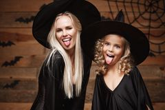 Halloween Concept - Closeup beautiful caucasian mother and her daughter in witch costumes celebrating Halloween posing with curved. Pumpkins over bats and Royalty Free Stock Photo