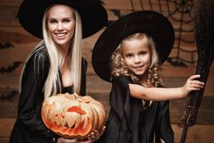 Halloween Concept - Closeup beautiful caucasian mother and her daughter in witch costumes celebrating Halloween posing with curved. Pumpkins over bats and stock image