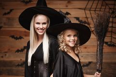 Halloween Concept - Closeup beautiful caucasian mother and her daughter in witch costumes celebrating Halloween posing with curved. Pumpkins over bats and royalty free stock images
