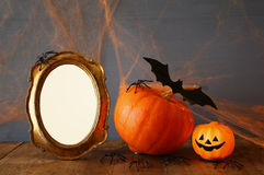 Halloween concept. Cute pumpkin next to blank photo frame Stock Image