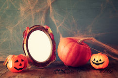 Halloween concept. Cute pumpkin next to blank photo frame Stock Photos