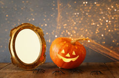 Halloween concept. Cute pumpkin next to blank photo frame Royalty Free Stock Image