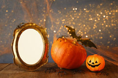 Halloween concept. Cute pumpkin next to blank photo frame Royalty Free Stock Images