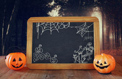 Halloween concept. Cute pumpkins next to blackboard Royalty Free Stock Image