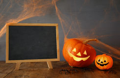 Halloween concept. Cute pumpkins next to blank blackboard Royalty Free Stock Photo