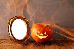 Halloween concept. Cute pumpkins next to blank photo frame Stock Photography