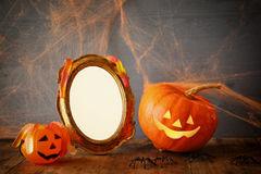 Halloween concept. Cute pumpkins next to blank photo frame Stock Images
