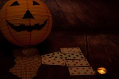 Halloween concept, darkness, candles, playing cards, pumpkin royalty free stock image