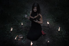 Halloween concept. Fairy in black. In the witchy circle. With a book of spells in hand. Inserts the spell into the book Royalty Free Stock Photos
