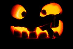 Halloween concept. The ghastly, ghastly pumpkin glows with a fie Royalty Free Stock Photos