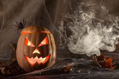 The ghastly, ghastly pumpkin glows with a fiery yellow light smoke and autumn leaves stock photo