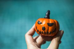 Halloween concept, girl hand holding funny pumpkin face Stock Image