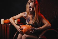 Halloween concept, girl vampire with red eyes red lips sit on rocking chair with pumpkins around. Scary woman trick or treat time stock photo