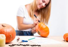 Halloween concept, happy Girl sitting at table with pumpkins preparing for holiday with candle and rope, drawing how to do Jack l. Antern, funny or spooky stock photo