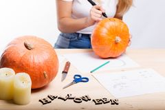 Halloween concept, happy Girl sitting at table with pumpkins preparing for holiday with candle and rope, drawing how to do Jack l. Antern, funny or spooky stock images