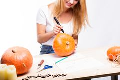 Halloween concept, happy Girl sitting at table with pumpkins preparing for holiday with candle and rope, drawing how to do Jack l. Antern, funny or spooky stock photography
