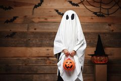 Halloween Concept - little white ghost with halloween pumpkin candy jar doing trick or treat with curved pumpkins over bats and sp. Ider web on Wooden studio stock image