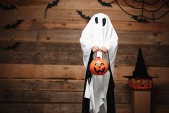 Halloween Concept - little white ghost with halloween pumpkin candy jar doing trick or treat with curved pumpkins over bats and sp royalty free stock photos