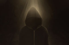 Halloween Concept, mysterious figure. Halloween Concept, A dark and sinister figure in a hood against black Stock Image