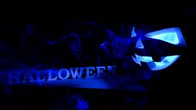 Halloween concept. An ominous pumpkin with Halloween inscription. With a cold blue glow and smoke, a poster for a party stock photo