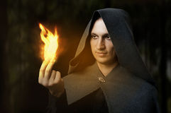 Halloween concept. Powerful Male witch. Or wizard with firel in hands. Ball from fire burns. Fantasy magic Stock Images