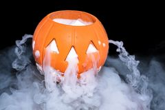 Halloween concept with pumpkin lantern & smoky the effect of dry ice. On darkness background royalty free stock photo