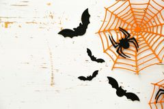 Halloween concept - spiders, bats, web paper crafts on bright background. Top view stock image