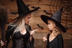 Halloween Concept - stressful witch mother teaching her daughter in witch costumes celebrating Halloween over bats and spider web. On Wooden studio background royalty free stock photography