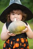 Funny little witch with pumpkin. Stock Photo