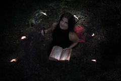 Halloween concept. Witch in black. In the witchy. Circle. With a satanic book in his hands. Looks up. Among woods and trees. Lighted candles of fire. Witchcraft Stock Photos
