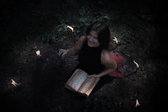 Halloween concept. Witch in black. In the witchy. Circle. With a satanic book in his hands. Looks up. Among woods and trees. Lighted candles of fire. Witchcraft Stock Photography