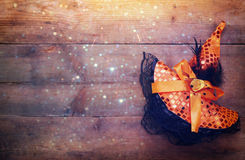 Halloween concept. Witch hat on wooden table. Halloween holiday concept. Witch hat on wooden table. Glitter overlay stock photo