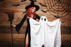 Halloween Concept - Witch mother and little white ghost doing trick or treat celebrating Halloween posing with curved pumpkins ove Stock Photo