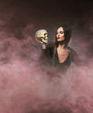 Halloween concept: young and sexy witch makes the witchcraft. In the dungeon Stock Image