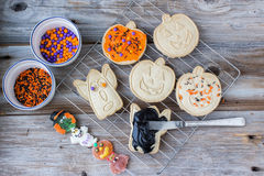 Halloween cookies on rack with icing and candy sprinkles on side Royalty Free Stock Photos