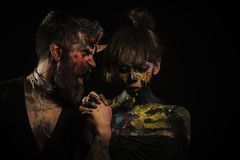 Halloween cosplay, holiday celebration. Couple in love on black background. Hipster devil shout at girl with skull makeup. Man with horns and women skeleton royalty free stock images