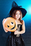 Halloween costume. Beautiful cute little girl in witch halloween costume hold the broom over dard background Stock Photography