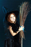 Halloween costume. Beautiful cute little girl in witch halloween costume hold the broom over dard background Royalty Free Stock Image