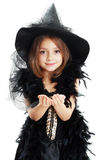 Halloween costume. Beautiful cute little girl in witch halloween costume smiling to the camera isolated over white holding something in her palms Stock Images