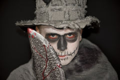 Halloween costume with a bloody meat cleaver. Young man standing in darkness wearing skull makeup, an old battered hat and Halloween costume holding up a bloody stock photos