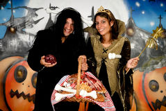Halloween couple graffiti. Young Halloween couple, female witch and man with sinister costume, basket with sweets.    Studio shot, graffiti  background Stock Image