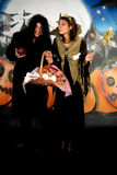 Halloween couple graffiti. Young Halloween couple, female witch and man with sinister costume, basket with sweets.    Studio shot, graffiti  background Royalty Free Stock Images