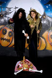 Halloween couple graffiti. Young Halloween couple, female witch and man with sinister costume, basket with sweets.    Studio shot, graffiti  background Royalty Free Stock Photo