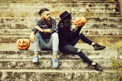 Halloween couple with pumpkin. Young halloween couple of bearded men smoking cigarette with beard and mustache and girl in black witch hat on stony stairs with stock image