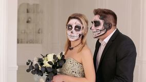 Halloween couple, woman and man with skull make-up. Halloween face art. Luxury young couple with halloween skull make-up in a dress and costume in a white room stock video footage