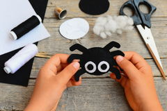 Small girl holds a felt spider ornament in his hand. Girl made a Halloween felt spider crafts. Easy felt crafts for beginners Royalty Free Stock Images